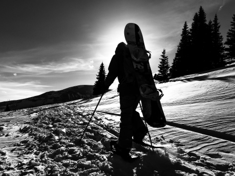A snowboarder hikes to the top of Hoosier Pass in search of fresh powder. Summit County, CO. February, 2017.