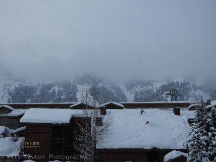 Skiers descend off the roof of The Inn at Jackson Hole after back to back storms in January, 2017.