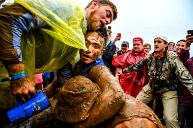 Patrons of the 143rd running of the Preakness Stakes wrestle in the mud of the infield after record rainfall hit the region in Baltimore, MD on May 19th, 2018. (Photo by Will Newton)