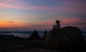A young park visitor sits on a rock awaiting the fourth of July fireworks from the top of Cadillac Mountain in Acadia National Park, ME on July 4, 2018. Photo by Will Newton/Friends of Acadia/NPS