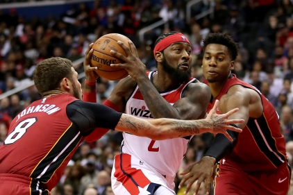 John Wall #2 of the Washington Wizards dribbles past Tyler Johnson #8 and Hassan Whiteside #21 of the Miami Heat during the second half at Capital One Arena on October 18, 2018 in Washington, DC. NOTE TO USER: User expressly acknowledges and agrees that, by downloading and or using this photograph, User is consenting to the terms and conditions of the Getty Images License Agreement. (Photo by Will Newton/Getty Images)