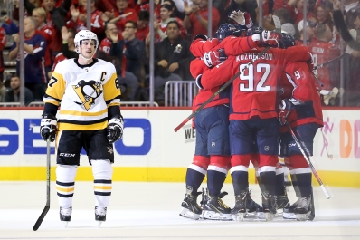 WASHINGTON, DC - NOVEMBER 07: Sidney Crosby #87 of the Pittsburgh Penguins skates past as T.J. Oshie #77 of the Washington Capitals celebrates with teammates after scoring the game winning goal during the third period at Capital One Arena on November 7, 2018 in Washington, DC. (Photo by Will Newton/Getty Images)
