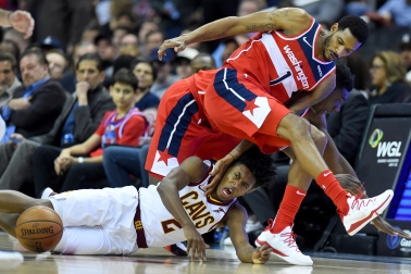 WASHINGTON, DC - FEBRUARY 08: Collin Sexton #2 of the Cleveland Cavaliers, Thomas Bryant #13 and Trevor Ariza #1 of the Washington Wizards dive after the ball during the first half at Capital One Arena on February 8, 2019 in Washington, DC. NOTE TO USER: User expressly acknowledges and agrees that, by downloading and or using this photograph, User is consenting to the terms and conditions of the Getty Images License Agreement. (Photo by Will Newton/Getty Images)