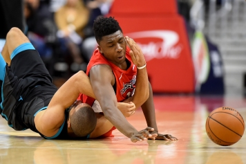 WASHINGTON, DC - DECEMBER 29: Thomas Bryant #13 of the Washington Wizards and Nicolas Batum #5 of the Charlotte Hornets dive after the ball during the second half at Capital One Arena on December 29, 2018 in Washington, DC. NOTE TO USER: User expressly acknowledges and agrees that, by downloading and or using this photograph, User is consenting to the terms and conditions of the Getty Images License Agreement. (Photo by Will Newton/Getty Images)