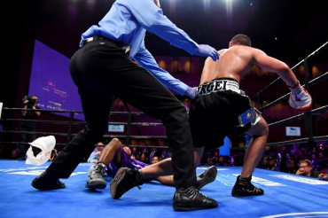 OXON HILL, MD - MARCH 24: Lamont Peterson's corner throws in the white towel as Sergey Lipinets is held back after knocking down Lamont Peterson during their welterweight fight at The Theater at MGM National Harbor on March 24, 2019 in Oxon Hill, Maryland. (Photo by Will Newton/Getty Images)