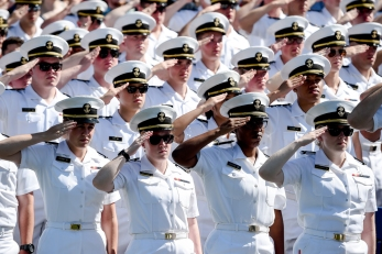 U.S Naval Academy midshipmen stand at attention for the National Anthem during the Academy's graduation and commissioning ceremony, Friday, May 24, 2019, in Annapolis, Md. (AP Photo/Will Newton)