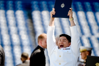A Naval Academy graduate celebrates after receiving their diploma during the Academy's graduation and commissioning ceremony, Friday, May 24, 2019, in Annapolis, Md. (AP Photo/Will Newton)