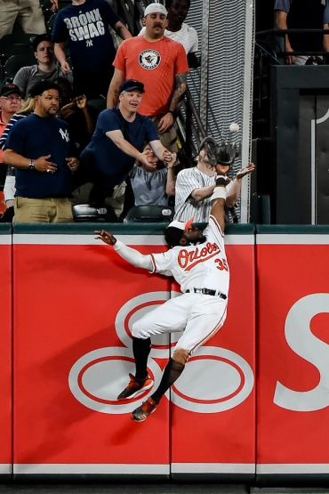 BALTIMORE, MD - MAY 20: Dwight Smith Jr. #35 of the Baltimore Orioles can't make the catch on a ball off the bat of Gleyber Torres #25 of the New York Yankees that cleared the wall for a home run in the eighth inning at Oriole Park at Camden Yards on May 20, 2019 in Baltimore, Maryland. (Photo by Will Newton/Getty Images)