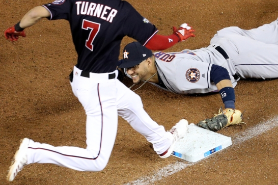WASHINGTON, DC - OCTOBER 27: Yuli Gurriel #10 of the Houston Astros dives to first base to tag out Trea Turner #7 of the Washington Nationals during Game Five of the 2019 World Series at Nationals Park on October 27, 2019 in Washington, DC. (Photo by Will Newton/Getty Images)