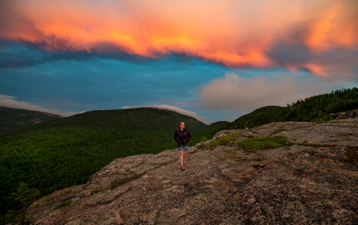 ACADIA NATIONAL PARK, ME - JULY 3: Park visitor Katie McElrath walks down the north ridge of the North Bubble as clouds are illuminated by the setting sun behind her in Acadia National Park, ME on July 3, 2020. (Photo by Will Newton/Friends of Acadia)