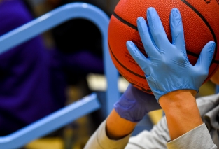 BALTIMORE, MD - MARCH 6: A gloved hand handles a game ball used during the game between Yeshiva and WPI at Johns Hopkins University in Baltimore, MD on March 6, 2020. (Photo by Will Newton for The Washington Post)