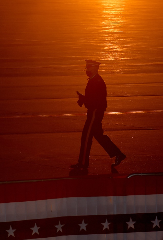 SUITLAND, MD - JANUARY 20: A member of the military is silhouetted by the rising sun prior to the arrival of President Donald Trump at Joint Base Andrews in Suitland, MD on January 20, 2021. (Photo by Will Newton for The Washington Post)