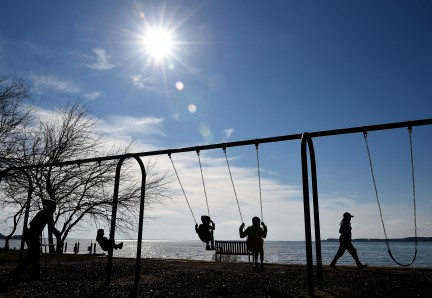 OXFORD, MD - FEBRUARY 5: Aukeem Cheers (L), of Easton, pushes his kids Haven Cheers, 3, Kade Cheers, 4, and Caleb Murray, 8, on a swing set in Oxford, MD on February 5, 2021. (Photo by Will Newton for The Washington Post)