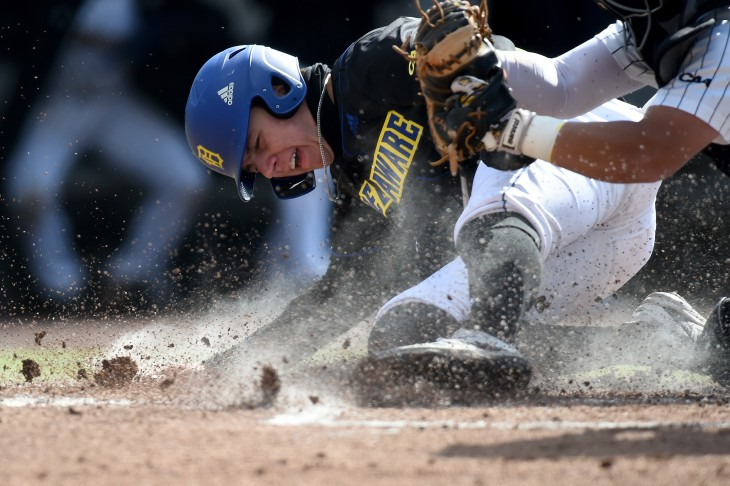 Delaware baserunner Aidan Kane (25) is tagged out at home by Towson catcher Jacob Terao (36) during an NCAA baseball game on Friday, April 2, 2021, in Towson, Md. (AP Photo/Will Newton)