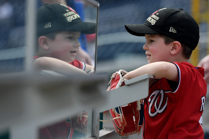 202104061716WN - A young fan watches batting practice before