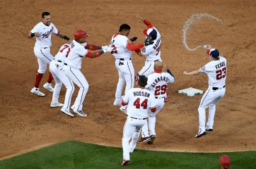 202104061716WN - Juan Soto #22 of the Washington Nationals celebrates with teammates after hitting a walk-off single to beat the Atlanta Braves after