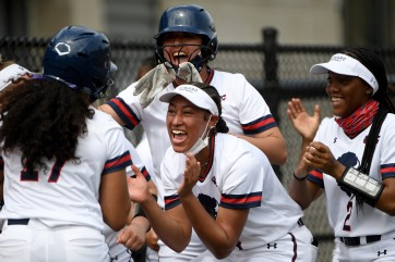 Howard batter Camille Navarro (L) is greeted by teammates after hitting a home run against Morgan St. during an NCAA softball game on Saturday, April 10, 2021, in Washington. (AP Photo/Will Newton)
